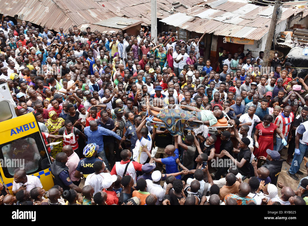Lagos, Nigeria. 13th Mar, 2019. People carry an injured person rescued from the scene of a building collapse in Lagos, Nigeria, on March 13, 2019. A school building in Lagos, Nigeria's commercial hub, on Wednesday collapsed with many primary school pupils feared dead, an eye witness and a local official said. Credit: NAN/Xinhua/Alamy Live News - Stock Image
