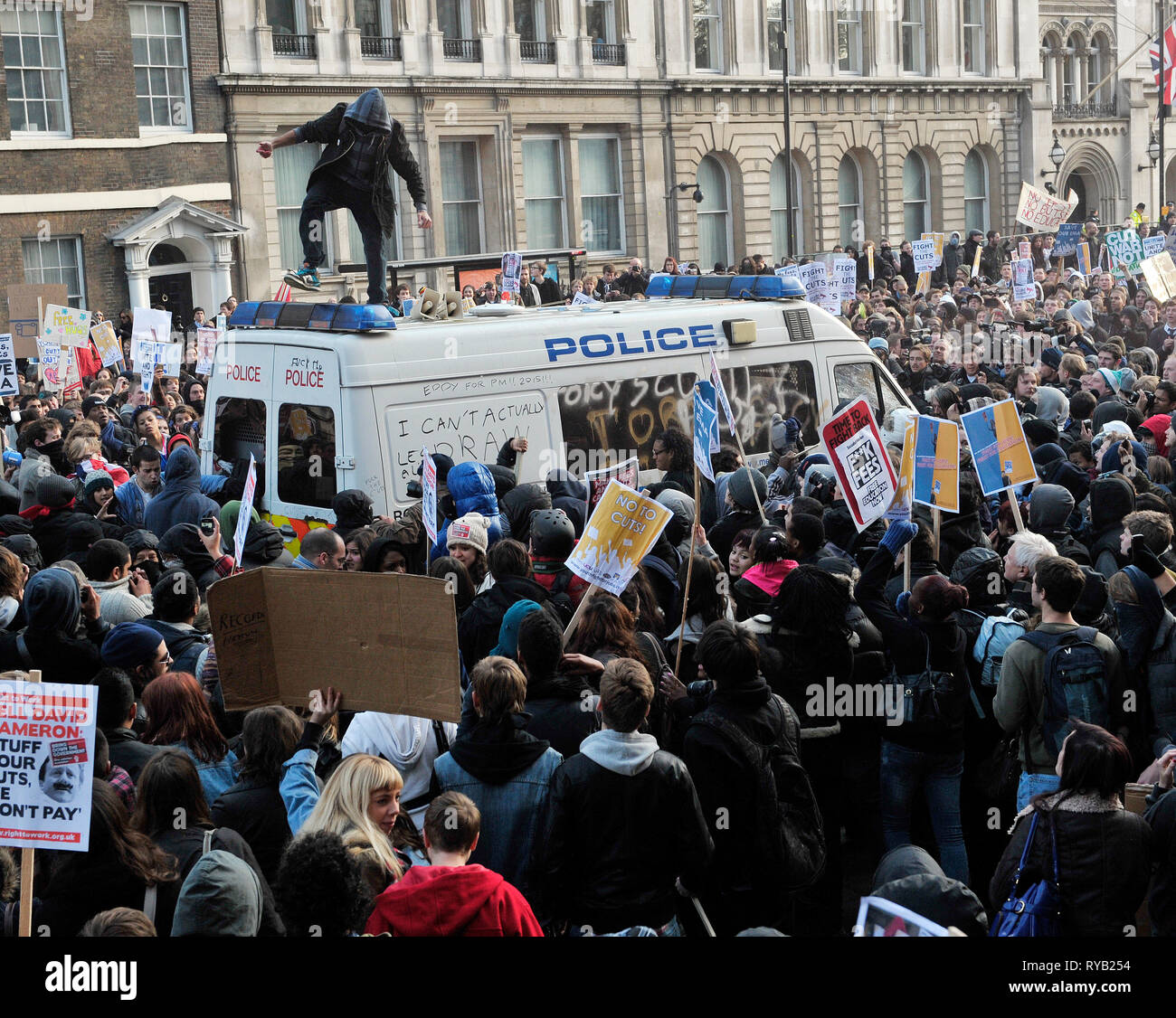 Student demos against govt cuts and top up fees . Trafalgar Square and Whitehall. A parked empty police van became the focus of many of the protestors' frustrations with small groups of hooded youths vandalising the vehicle: clambering onto the roof, writing  graffiti on the body work and smashing its windows and sirens . The presence of the van however alerted suspicions with many demonstrators alleging that the vehicle had been placed deliberately as a target which could then be retrospectively cited as  justification for heavier handed police intervention or to simply further isolate the st - Stock Image