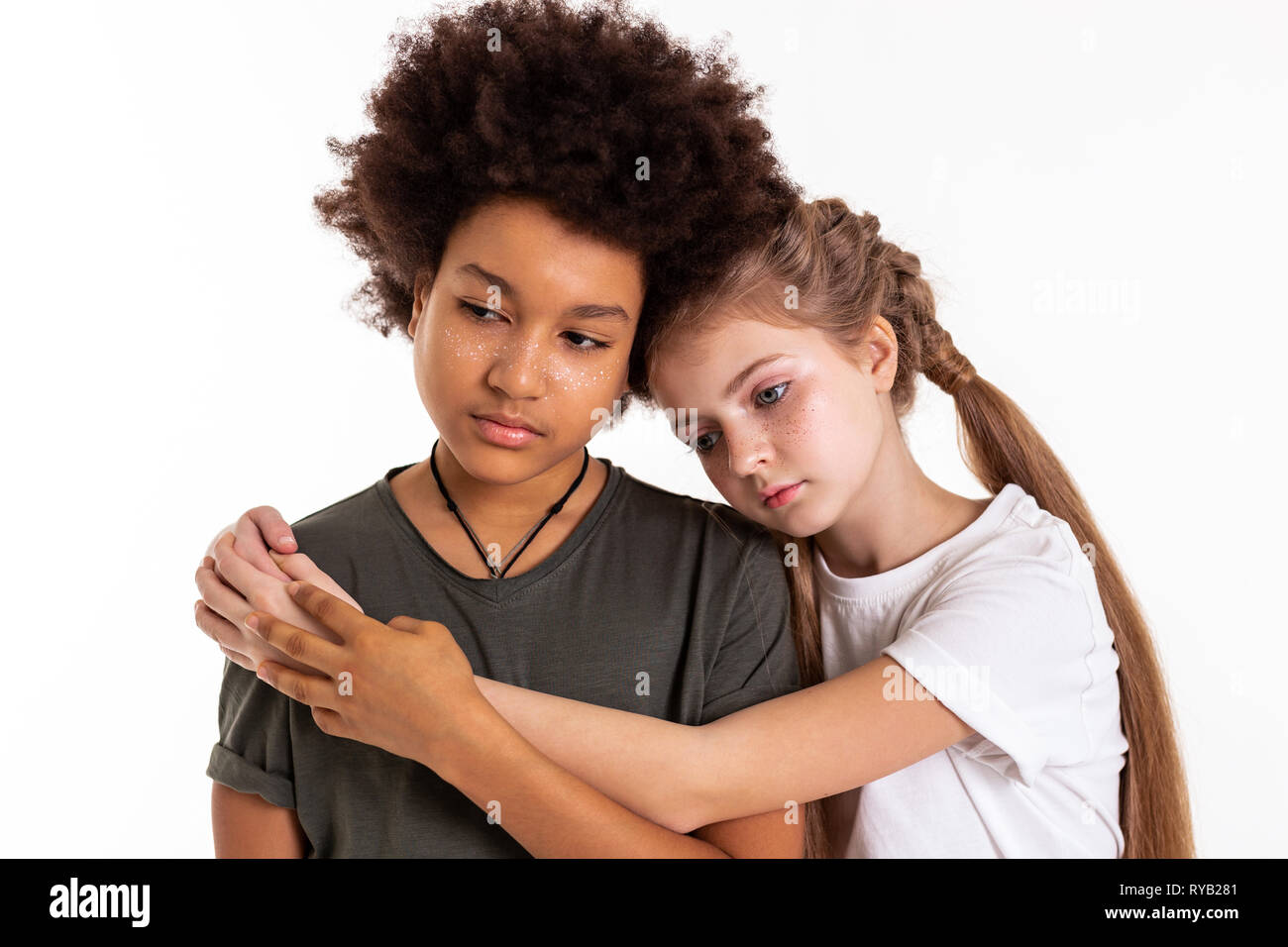 Pleasant calm children staying together and hugging - Stock Image