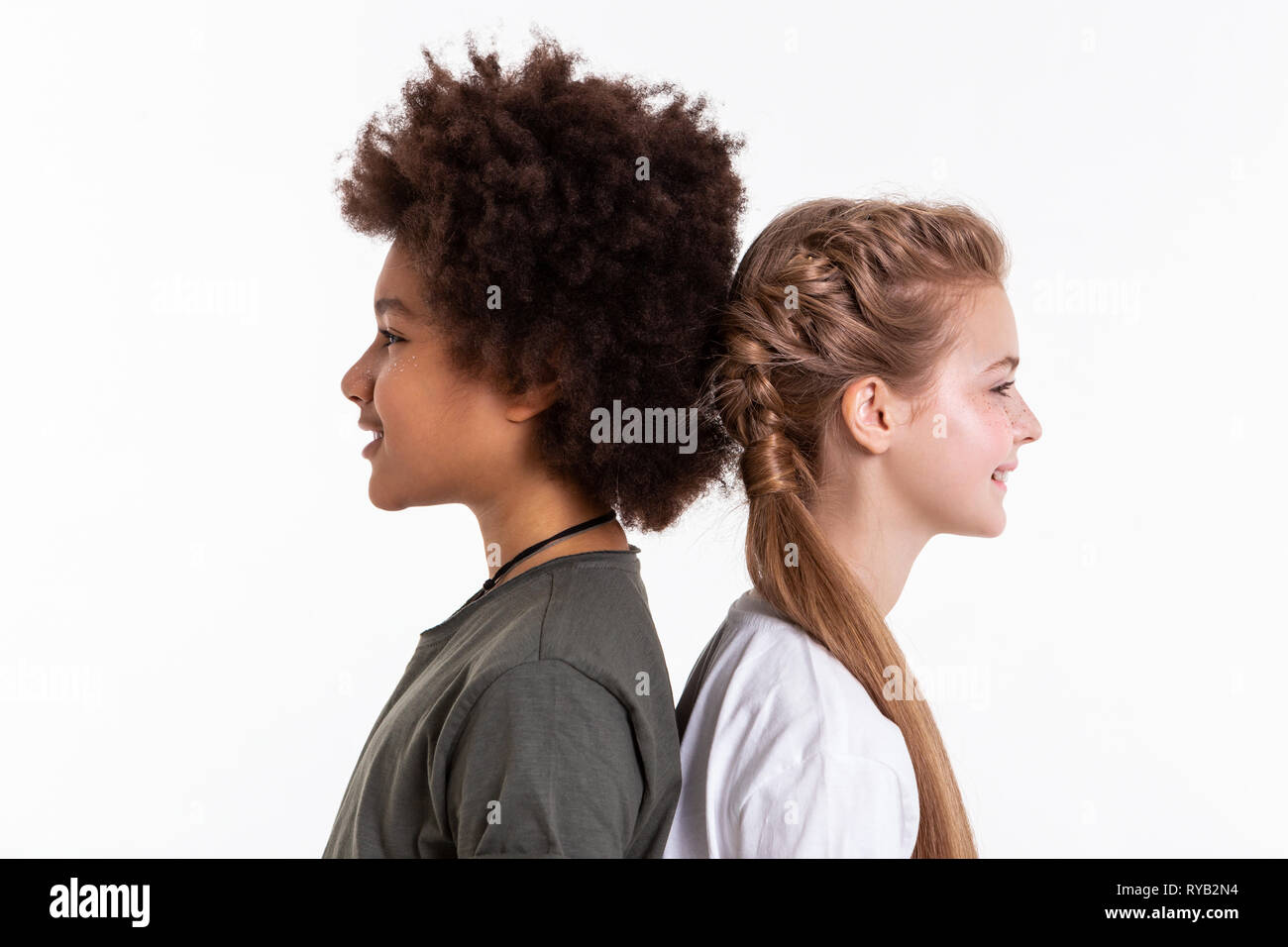 Beaming young unusual friends staying extremely close to each other - Stock Image