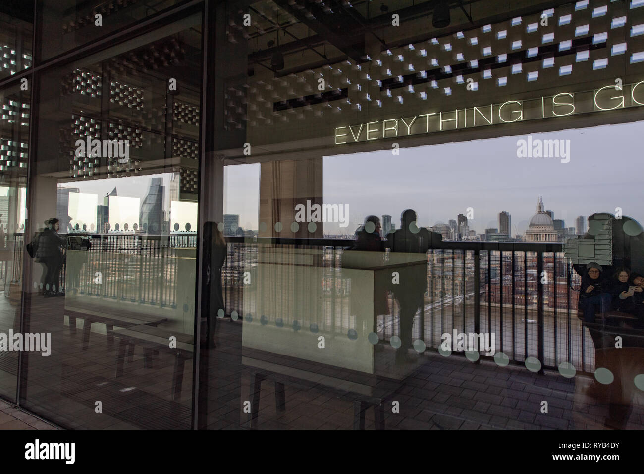 Reflection of people looking over balcony at the Tate Modern Gallery at London city view including St Paul's Cathedral.  London. Stock Photo