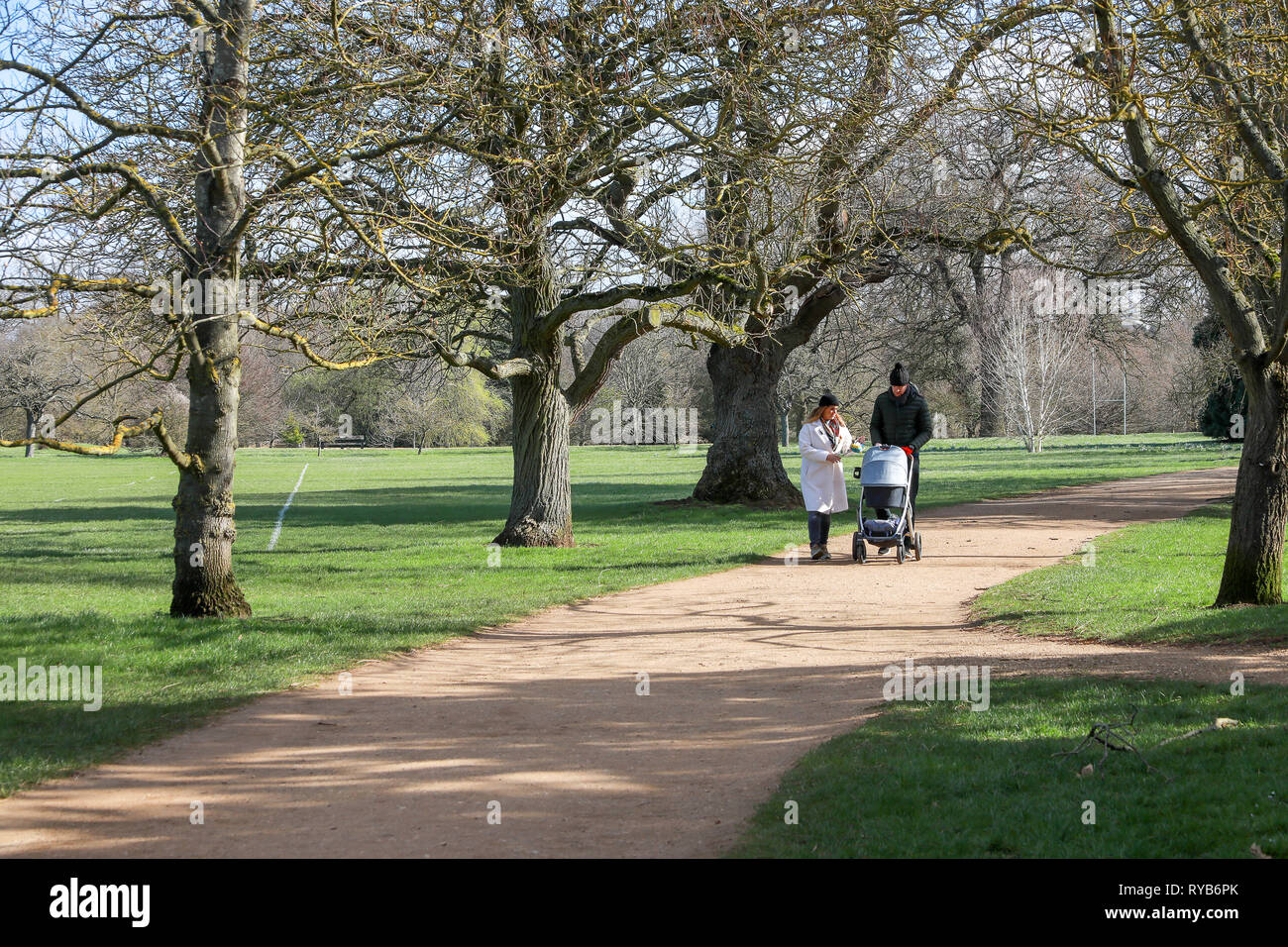 Mother and father walking with a buggy stroller pram on a gravel path in the sunshine in Oxford University Parks in winter / spring - Stock Image