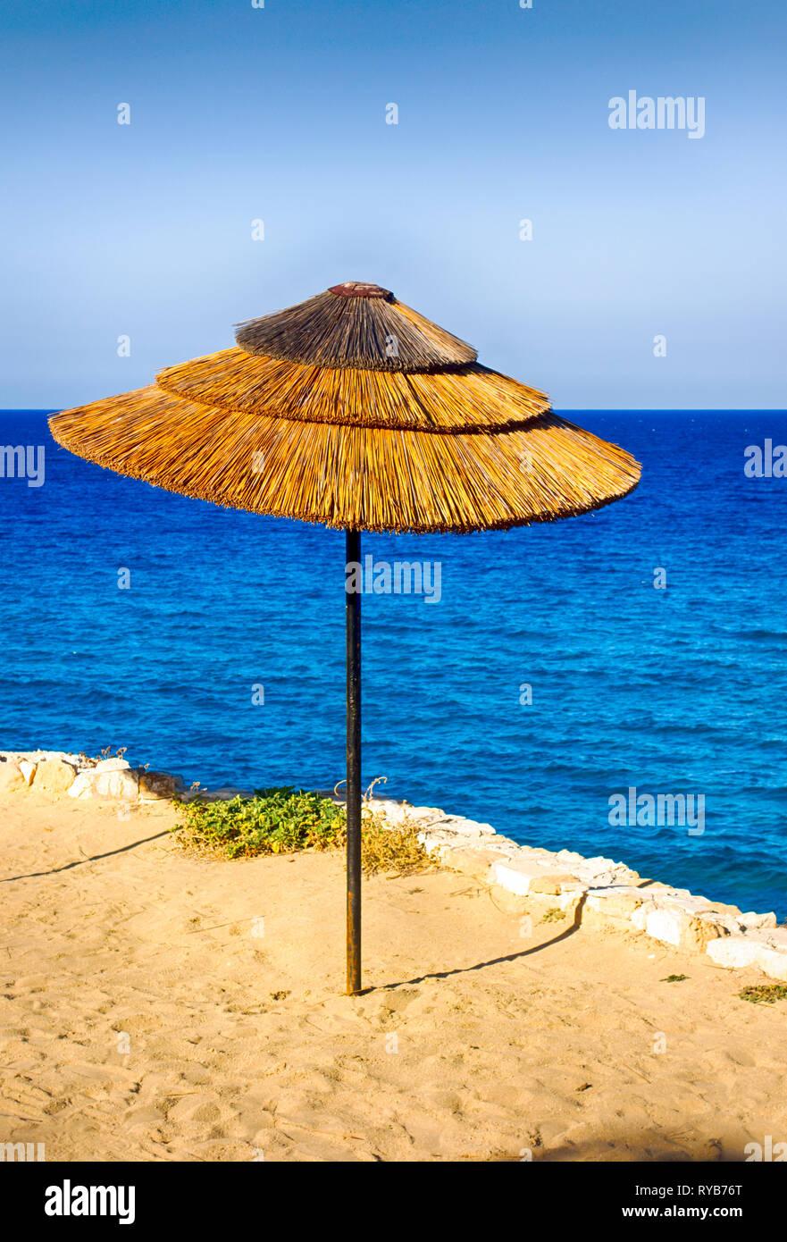 Straw beach umbrella on the sea beach. - Stock Image