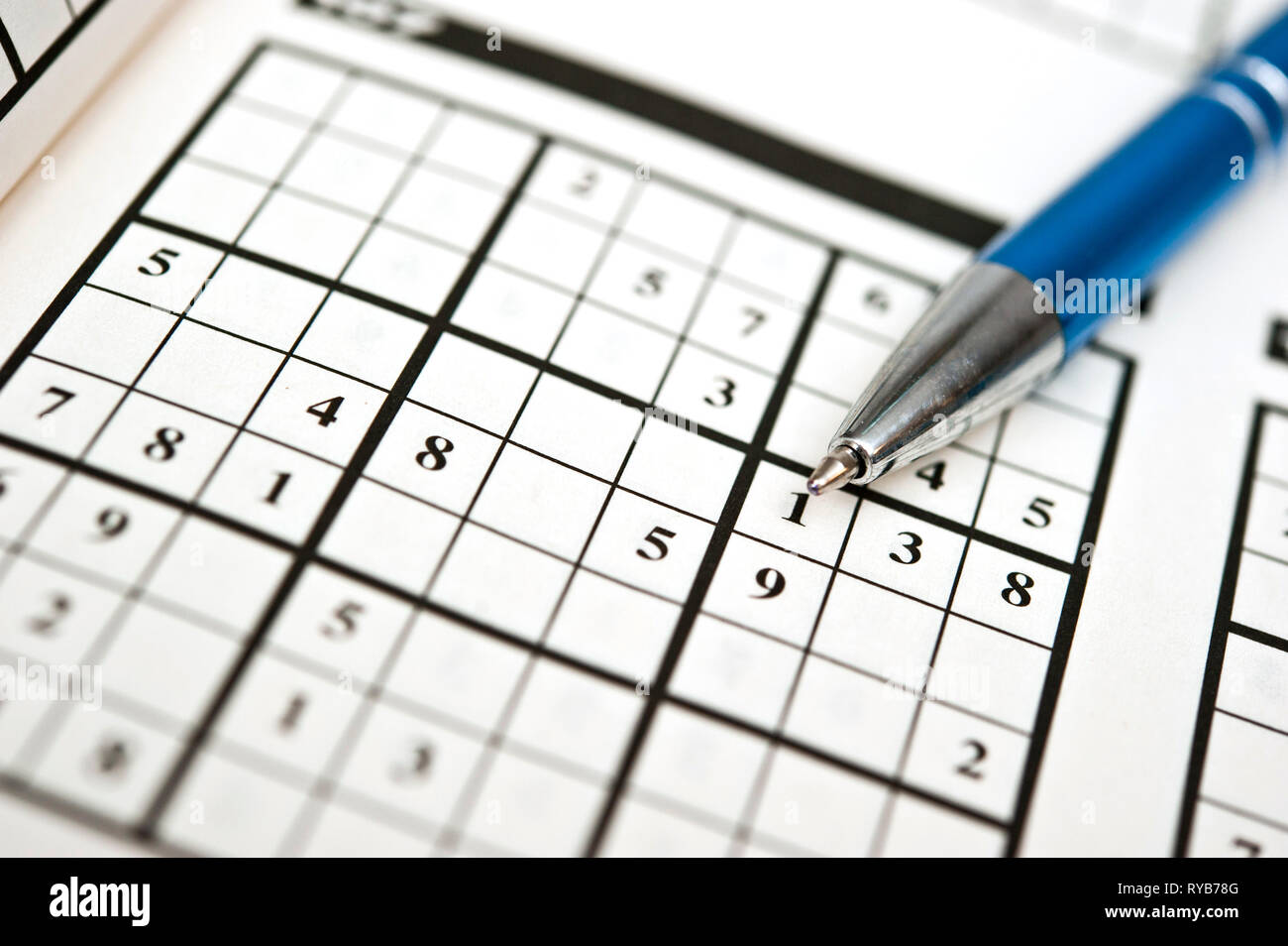 blue pen and a book with Sudoku puzzles to solve - Stock Image