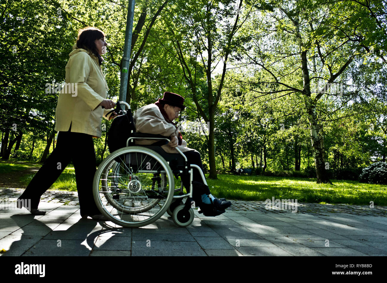 helper pushing an elder disabled woman on wheelchair in the park - Stock Image