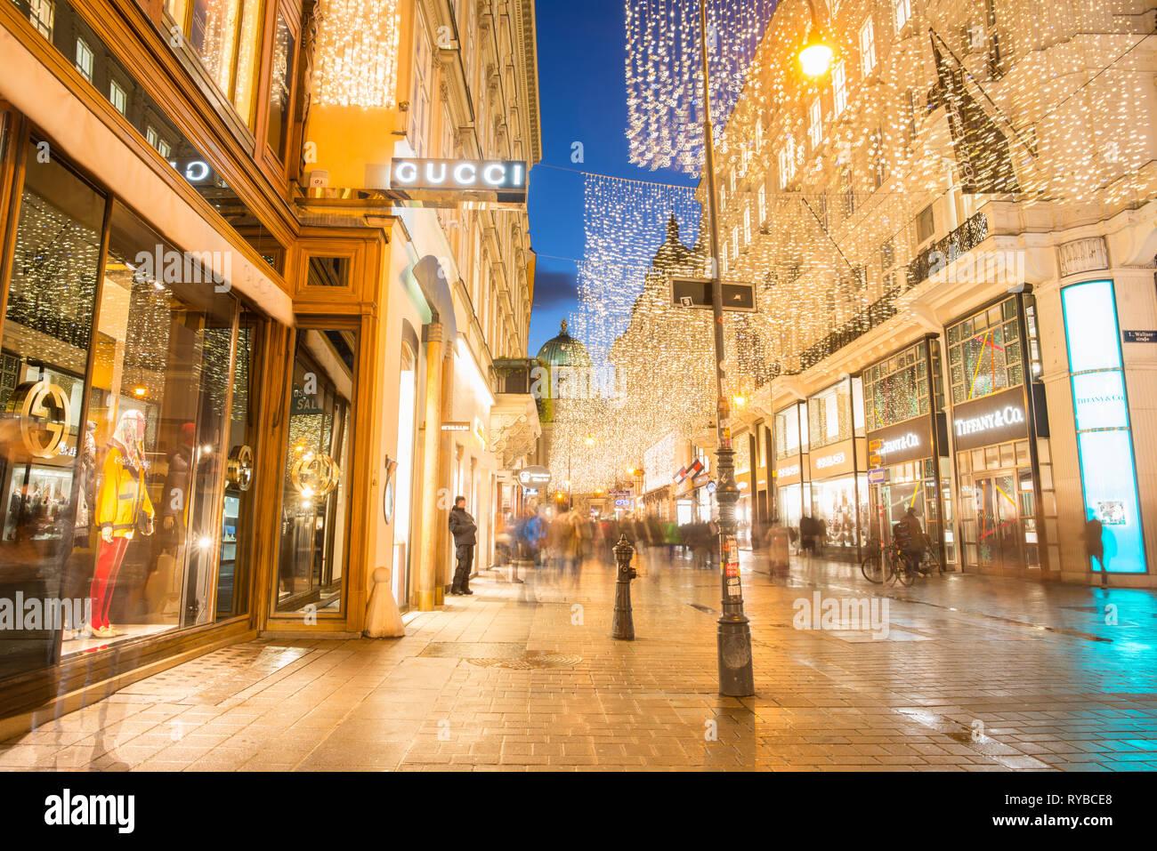 Upmarket Kohlmarkt with Hofburg palace to the rear, in Vienna city centre after dark, Austria. - Stock Image