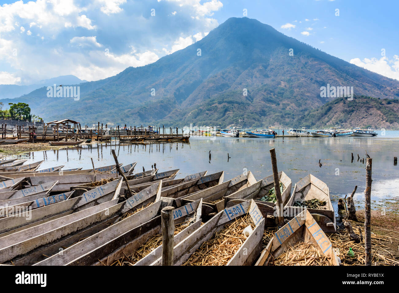 Santiago Atitlan, Lake Atitlan, Guatemala - March 8, 2019: Rows of lakeside traditional canoes with San Pedro volcano behind in largest lakeside town - Stock Image