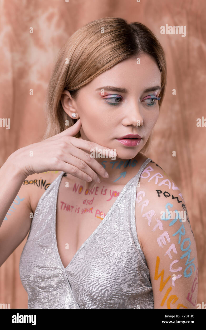 Serious pleasant nice woman touching her cheek - Stock Image