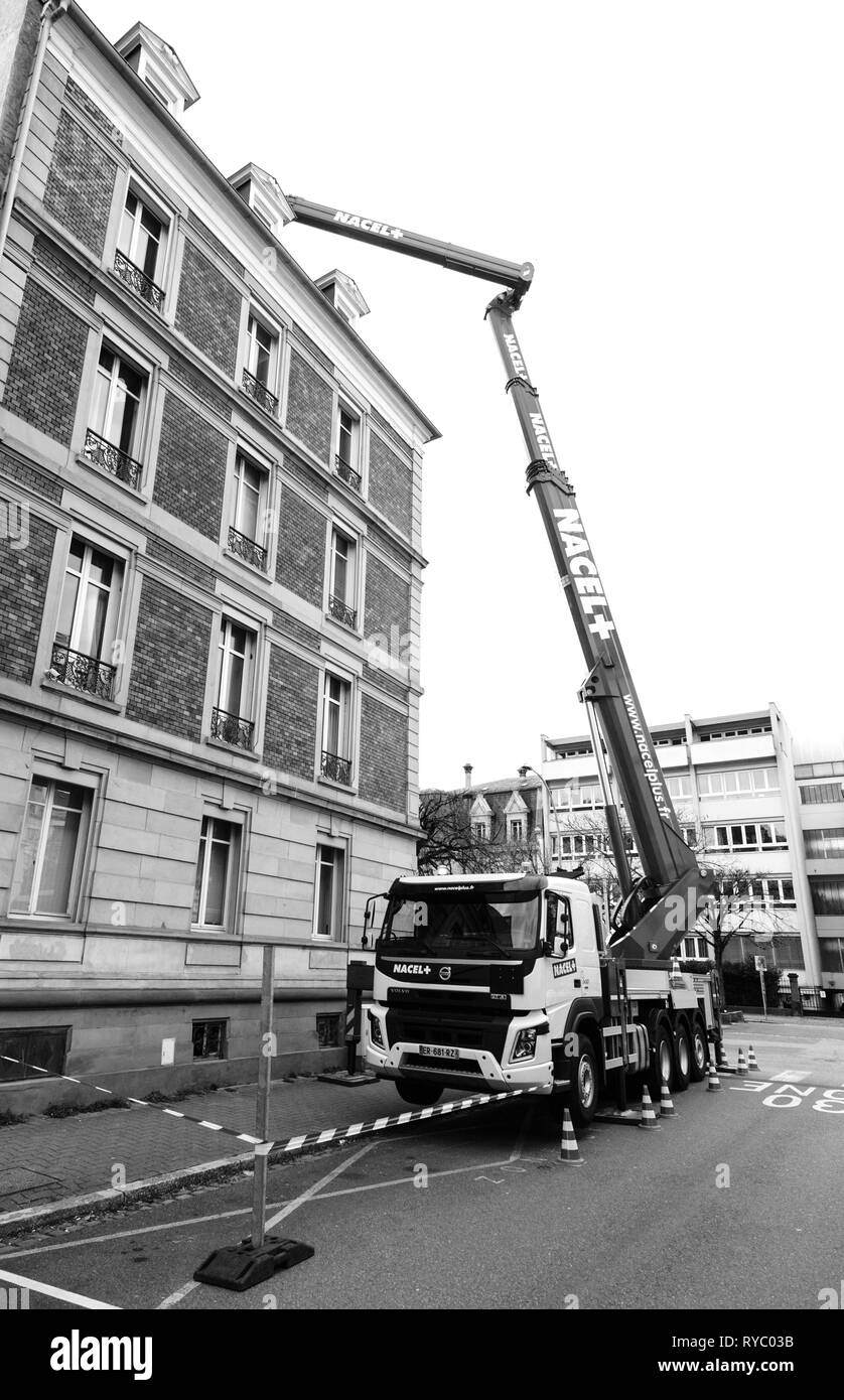 Strasbourg, France - Dec 13, 2019: Volvo Truck FMx with new nacelle manipulator hydraulic lifter lifting cargo on roof of the luxury French building during repair construction  - Stock Image