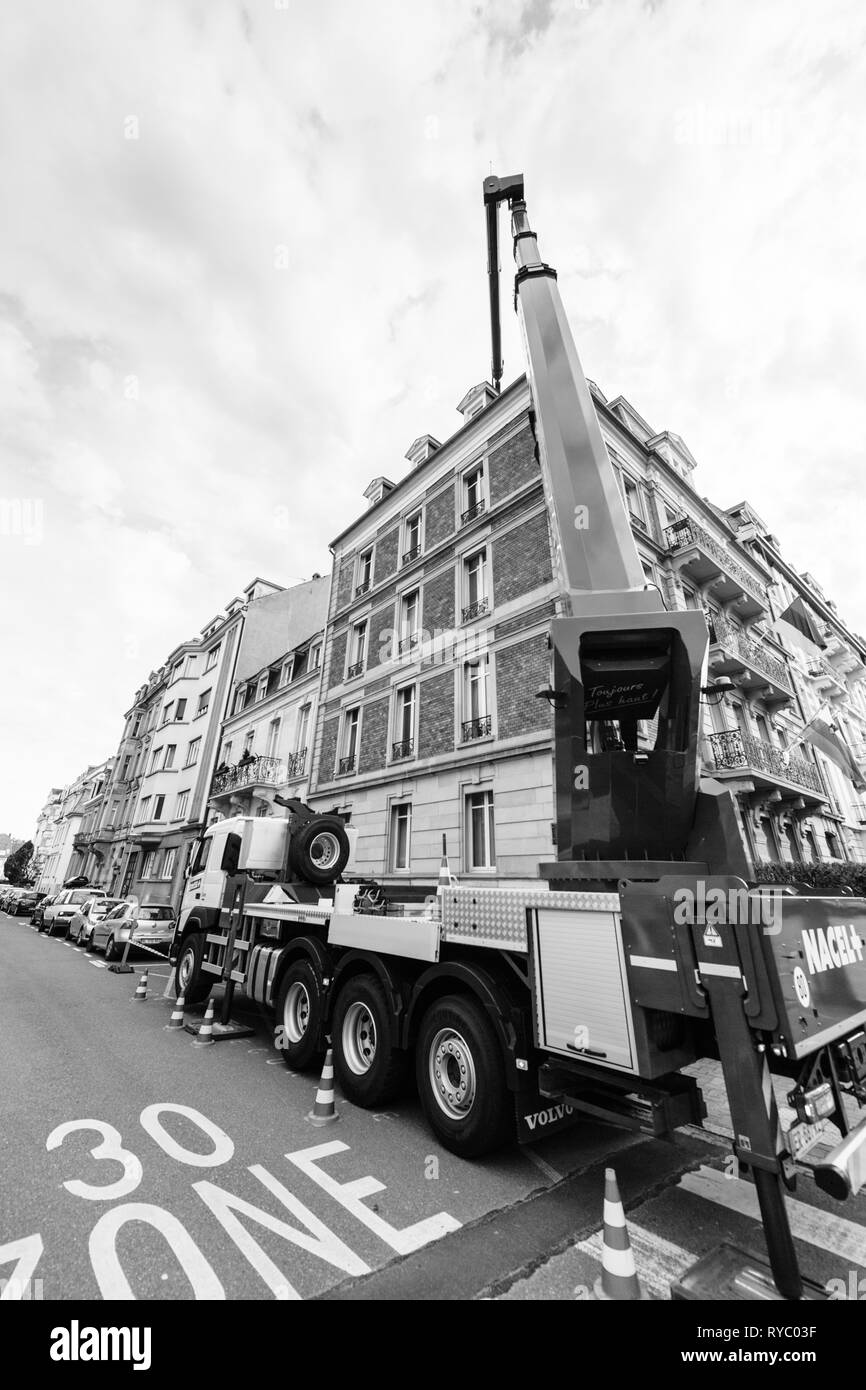 Strasbourg, France - Dec 13, 2019: Rear view of Volvo Truck FMx with new nacelle manipulator hydraulic lifter lifting cargo on roof of the luxury French building during repair construction  - Stock Image