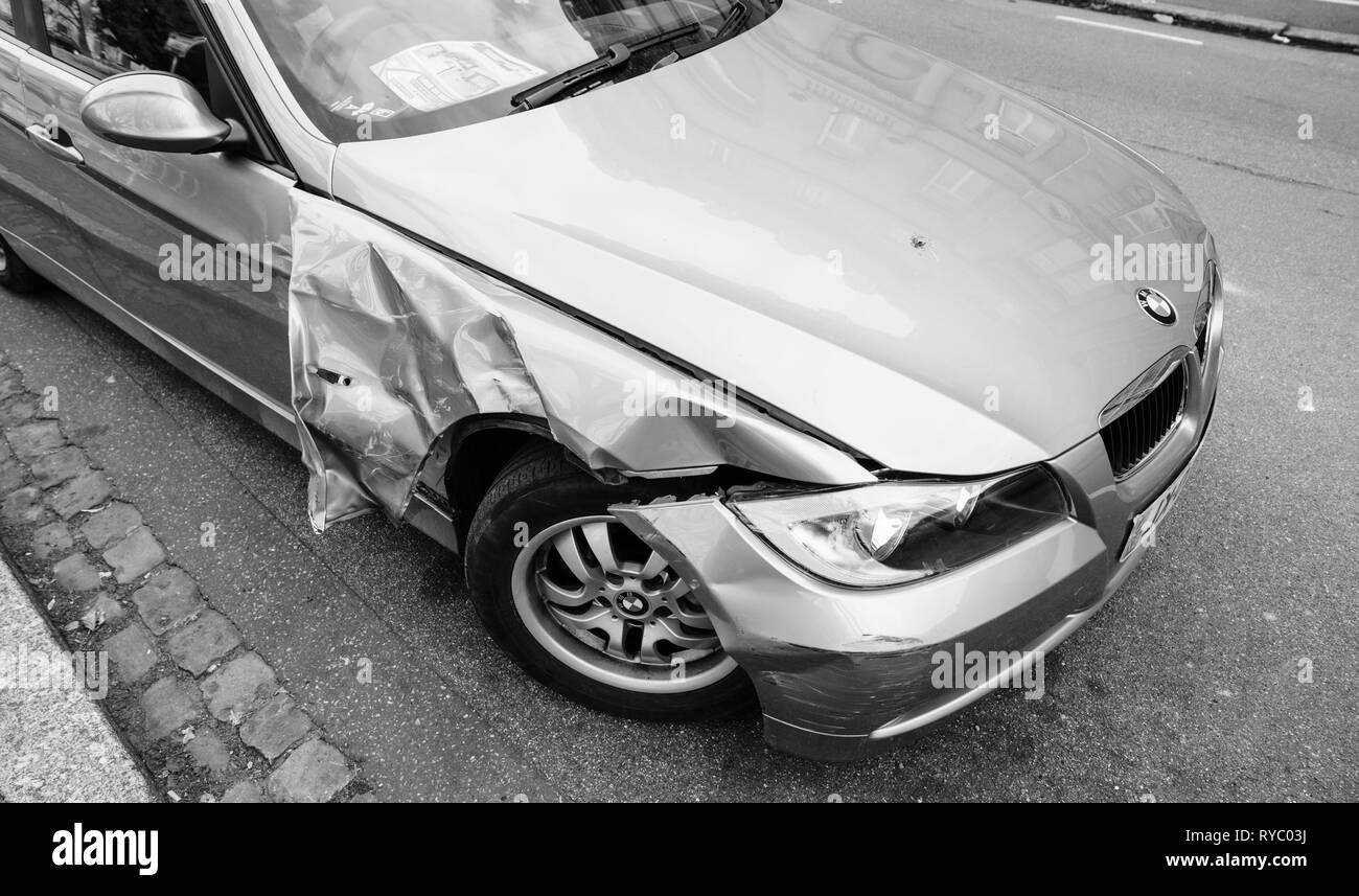 Strasbourg, France - Mar 12, 2019: Black and white image of luxury BMW german car parked on city street with damaged front by accident on the road - Stock Image