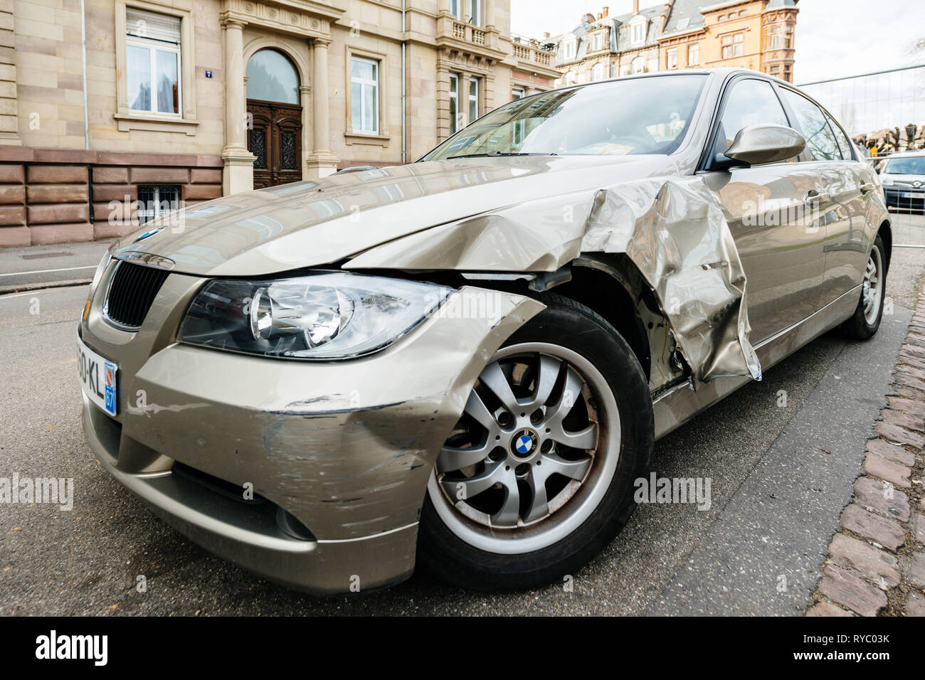 Strasbourg, France - Mar 12, 2019: Detail of luxury BMW german car parked on city street with damaged front by accident on the road - Stock Image