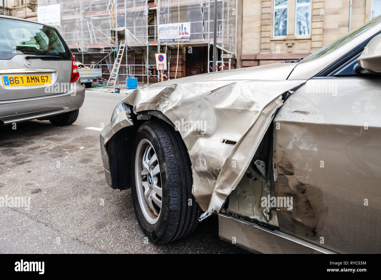Strasbourg, France - Mar 12, 2019: Side view of luxury BMW german car parked on city street with damaged front by accident on the road - Stock Image