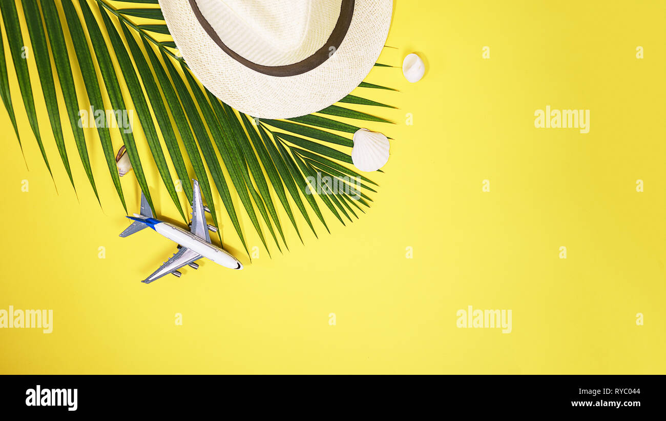 b22b47f6 Flat lay traveler accessories: tropical palm leaf branches, white straw  hat, airplane toy and seashells on yellow background with space for text.