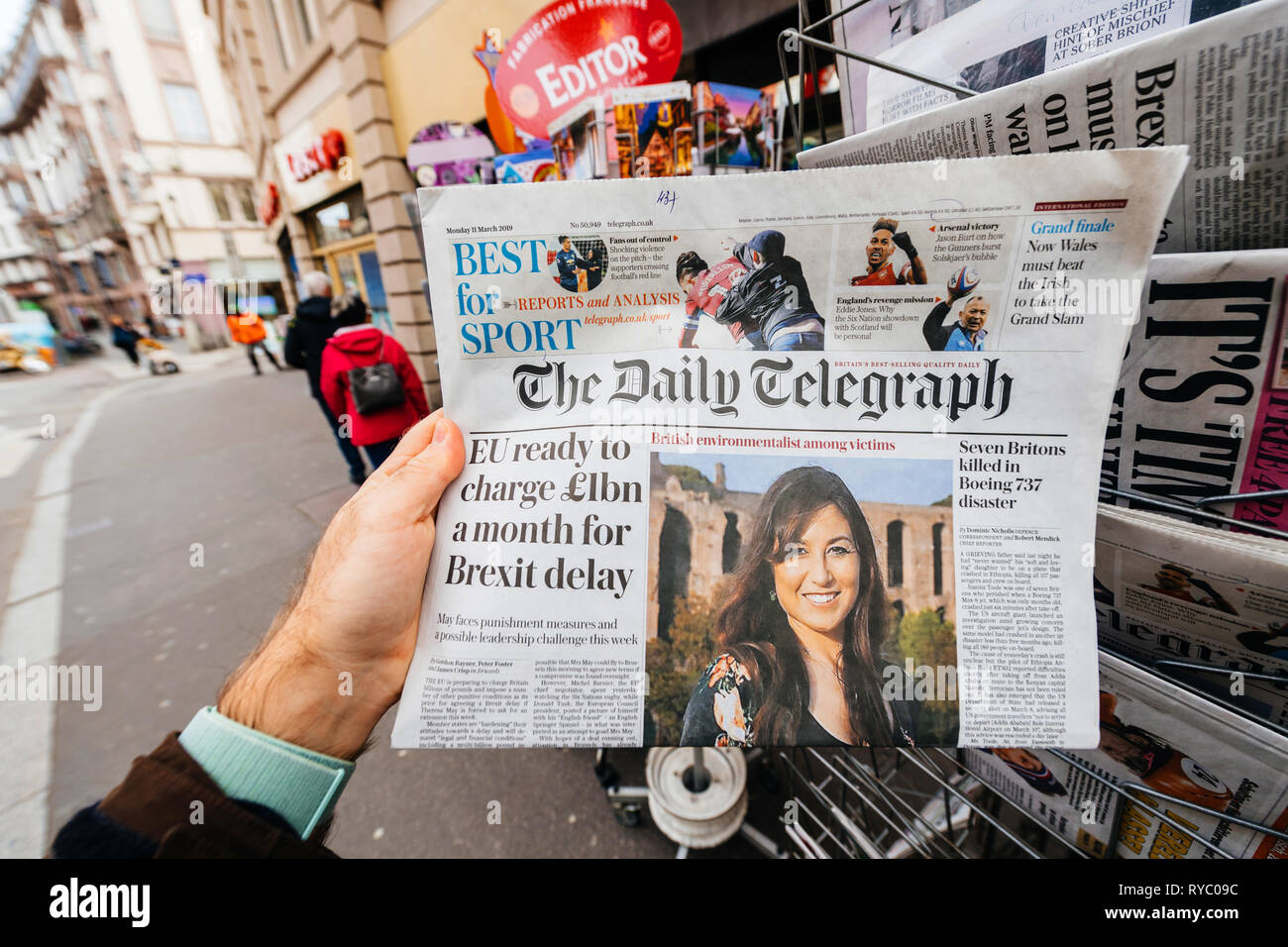 Paris, France - Mar 12, 2019: Man buying press kiosk British newspaper The Daily Telegraph featuring on the cover text that Eu ready to charge 1 billion a month for Brexit delay - Stock Image