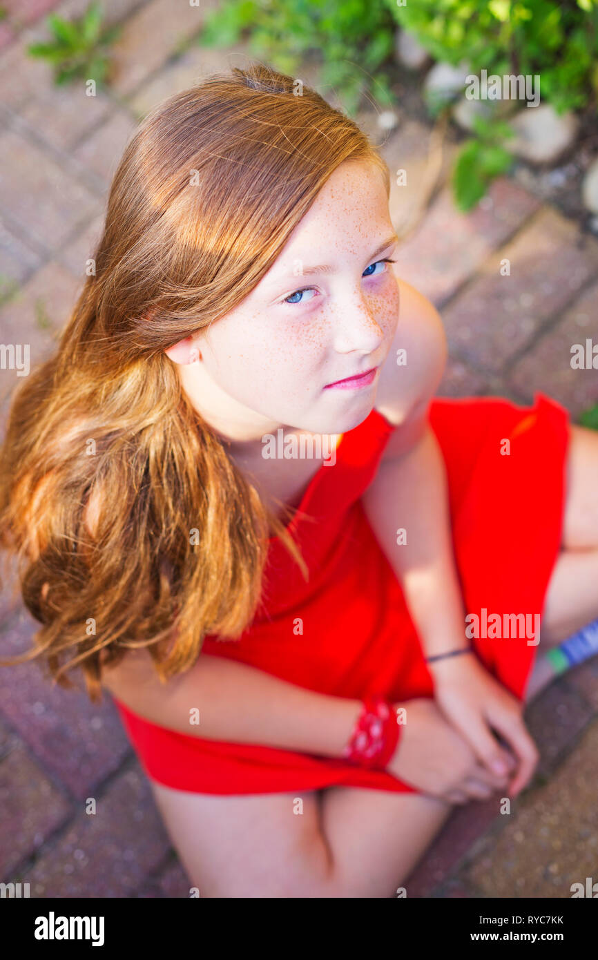 A young teenage girl with red hair and red dress - Stock Image