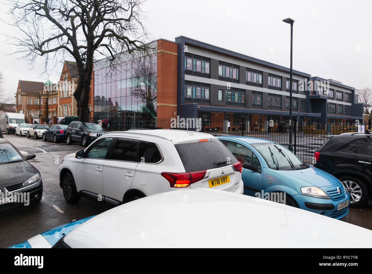 Cars parked dangerously / badly / illegally / double parking / double parked with hazard lights flashing during the school run drop off / collection UK - Stock Image