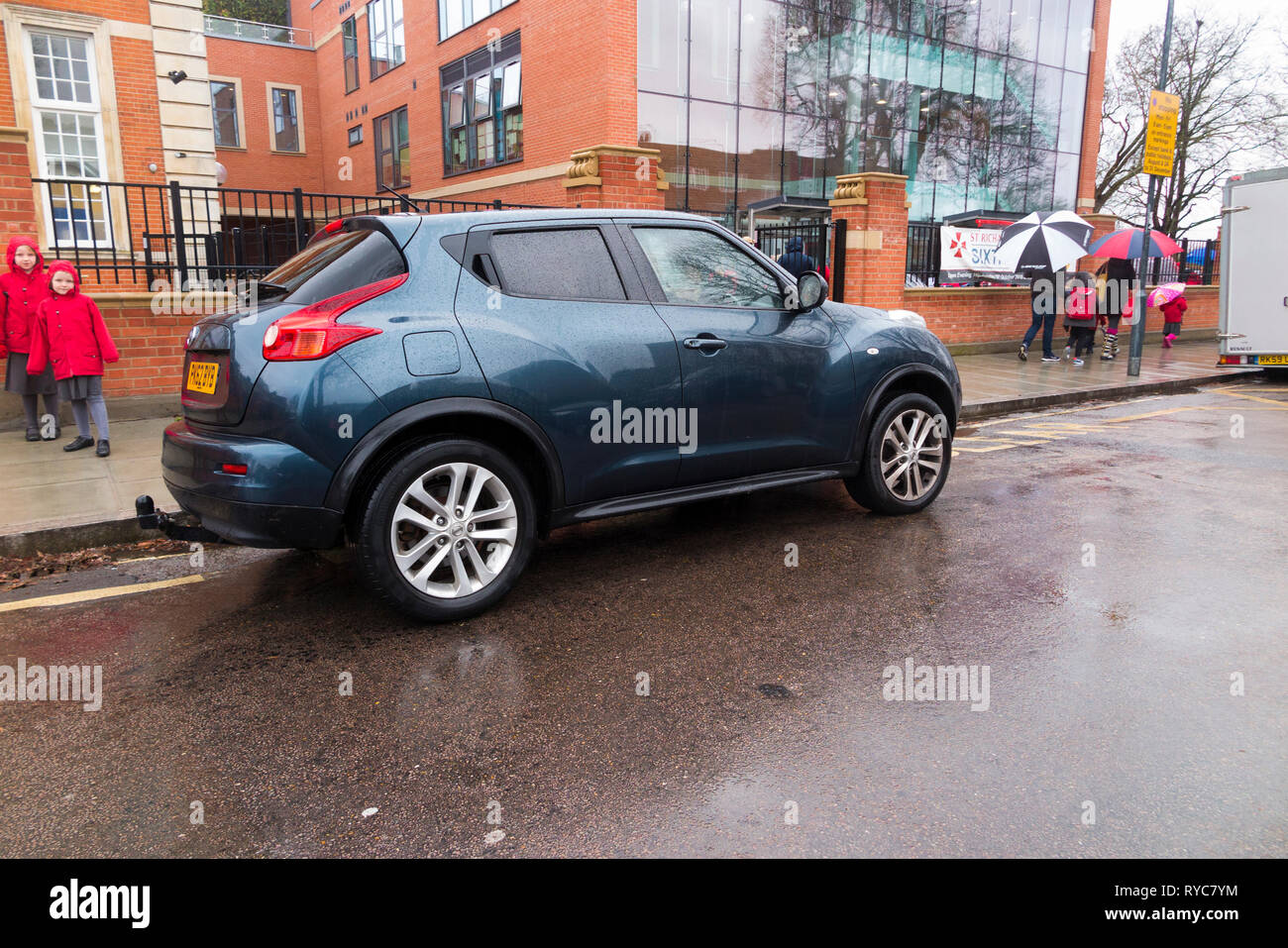 Cars parked on zigzag / zig zag yellow no parking lines; dangerously / badly / illegally during the school run drop off / collection. UK. (107) - Stock Image
