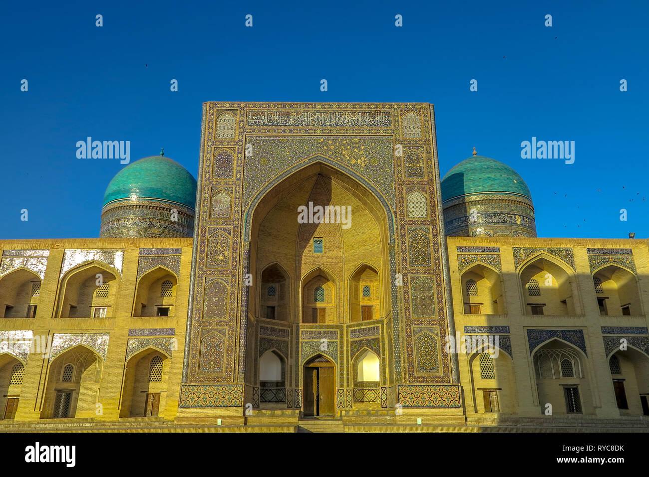 Bukhara Old City Arabian Miri Arab Madrasa Iwan with Blue Tiles Domes Main Gate Entrance Viewpoint at Sunset - Stock Image