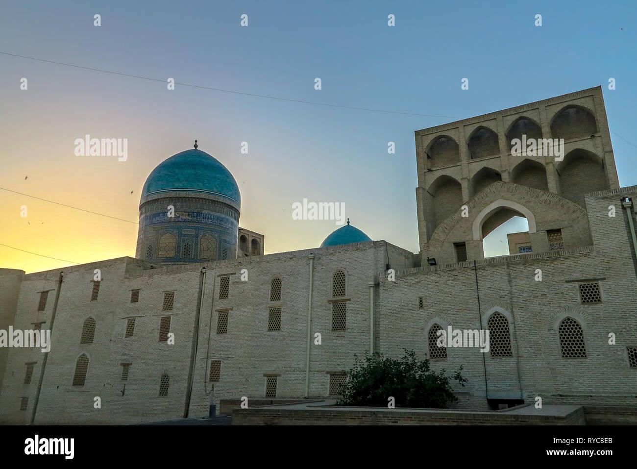 Bukhara Old City Arabian Miri Arab Madrasa Facade Walls Back View at Sunset - Stock Image