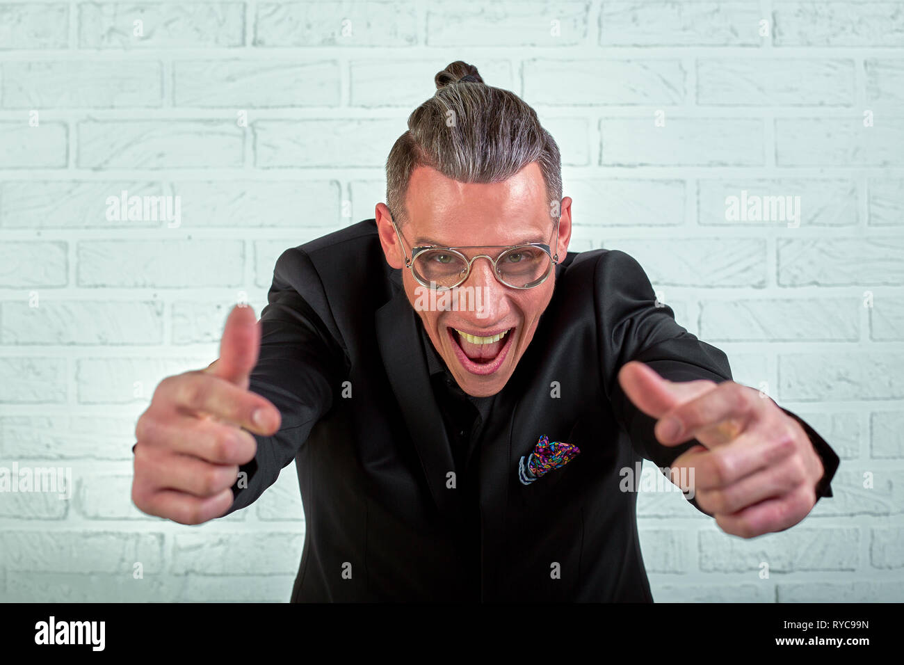 Close up portrait of a happy young businessman wearing glasses dressed in a black suit shows hands cool - Stock Image