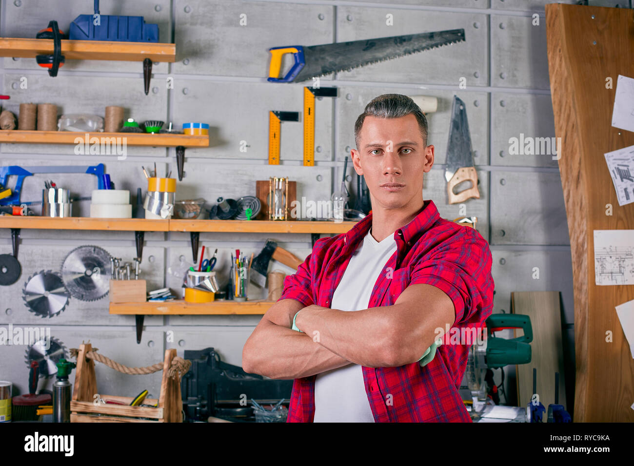 locksmith stands in the workshop on the background of the wall with shelves under the tools - Stock Image
