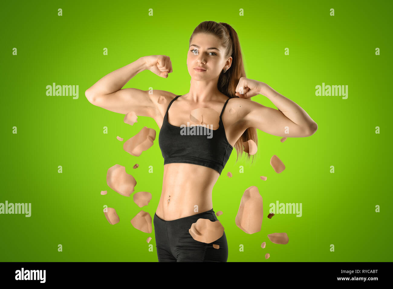 Young fit woman standing half-turn and performing double bicep pose with pieces of flesh in air around her body on green background. - Stock Image
