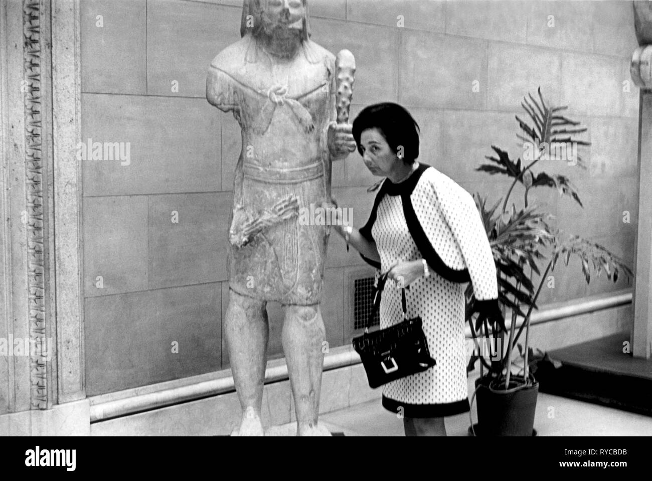 A woman knocks on a ancient statue to check if it is stone or wood. New York 1969. USA Its stone. .60s US  HOMER SYKES - Stock Image
