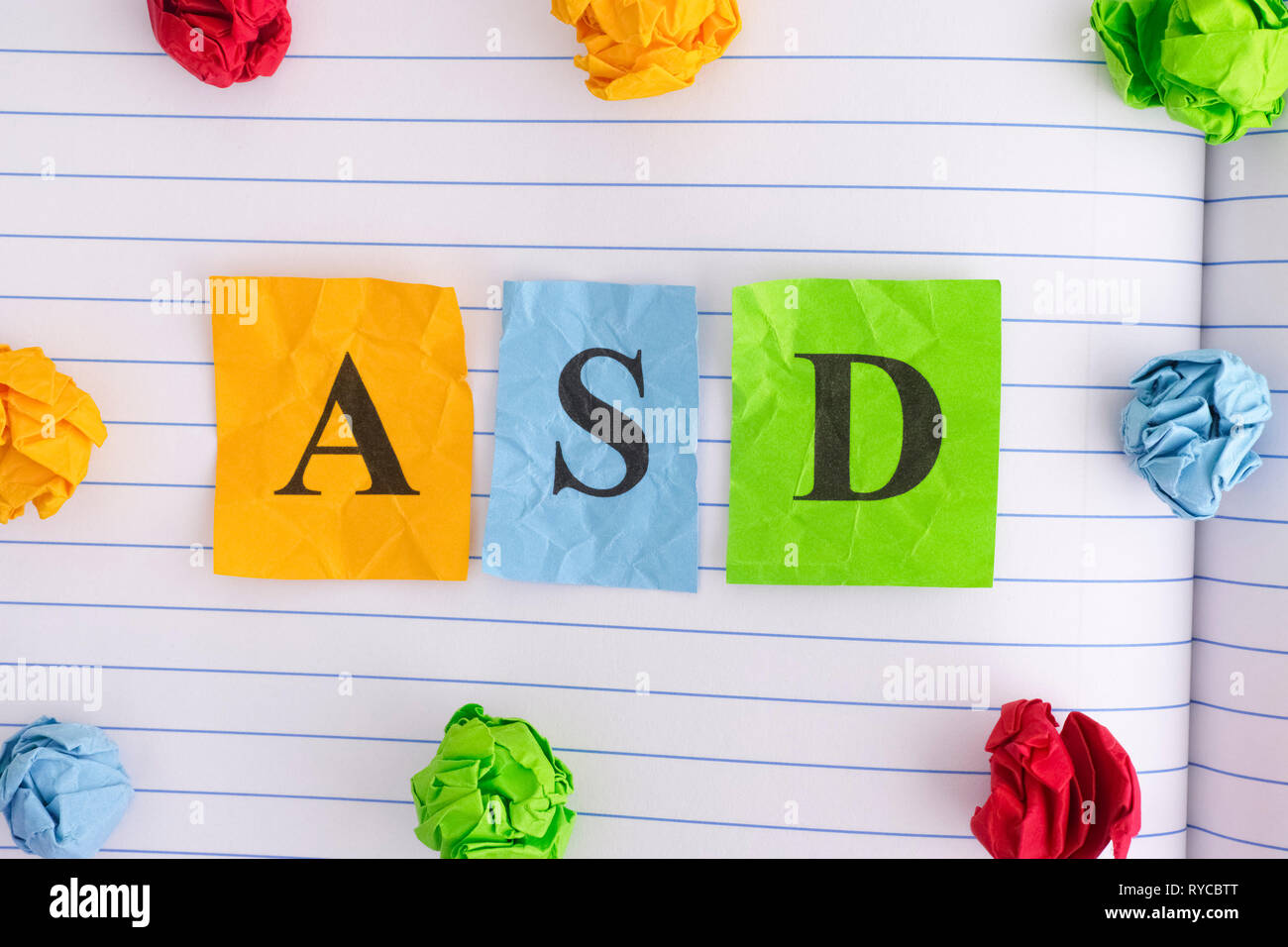 ASD. ASD (Autism spectrum disorder) on notebook sheet with some colorful crumpled paper balls around it. Close up. - Stock Image