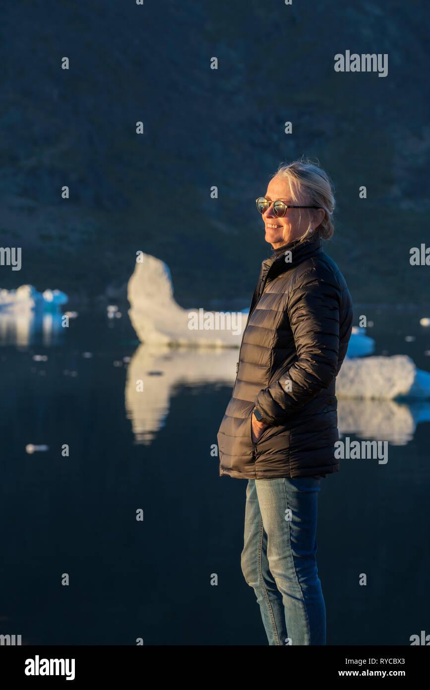 Female enjoying the evening sunshine, South Greenland - Stock Image