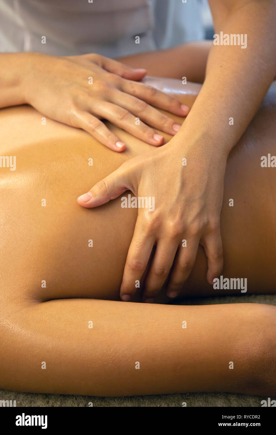 Close up on the hands of a masseuse during a massage treatment in a Spa in Ierapetra town, Crete, Greece. - Stock Image