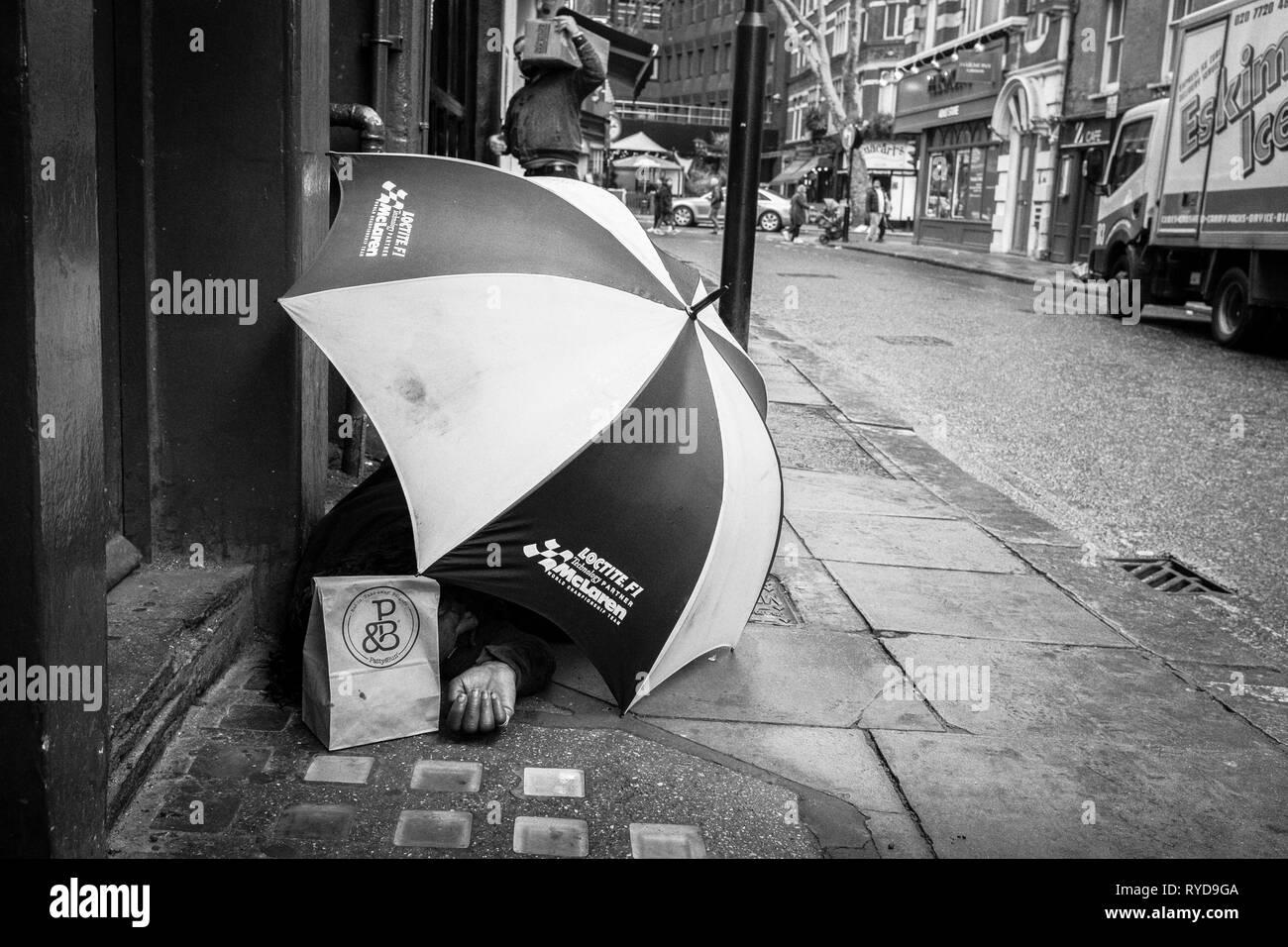 Homeless man using large umbrella for shelter on central London street. UK - Stock Image
