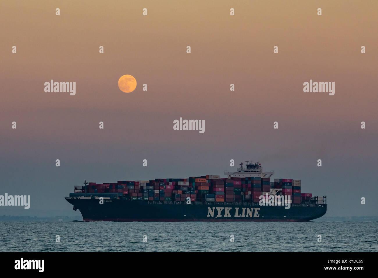 Cargo Ship under a Full Moon - Stock Image