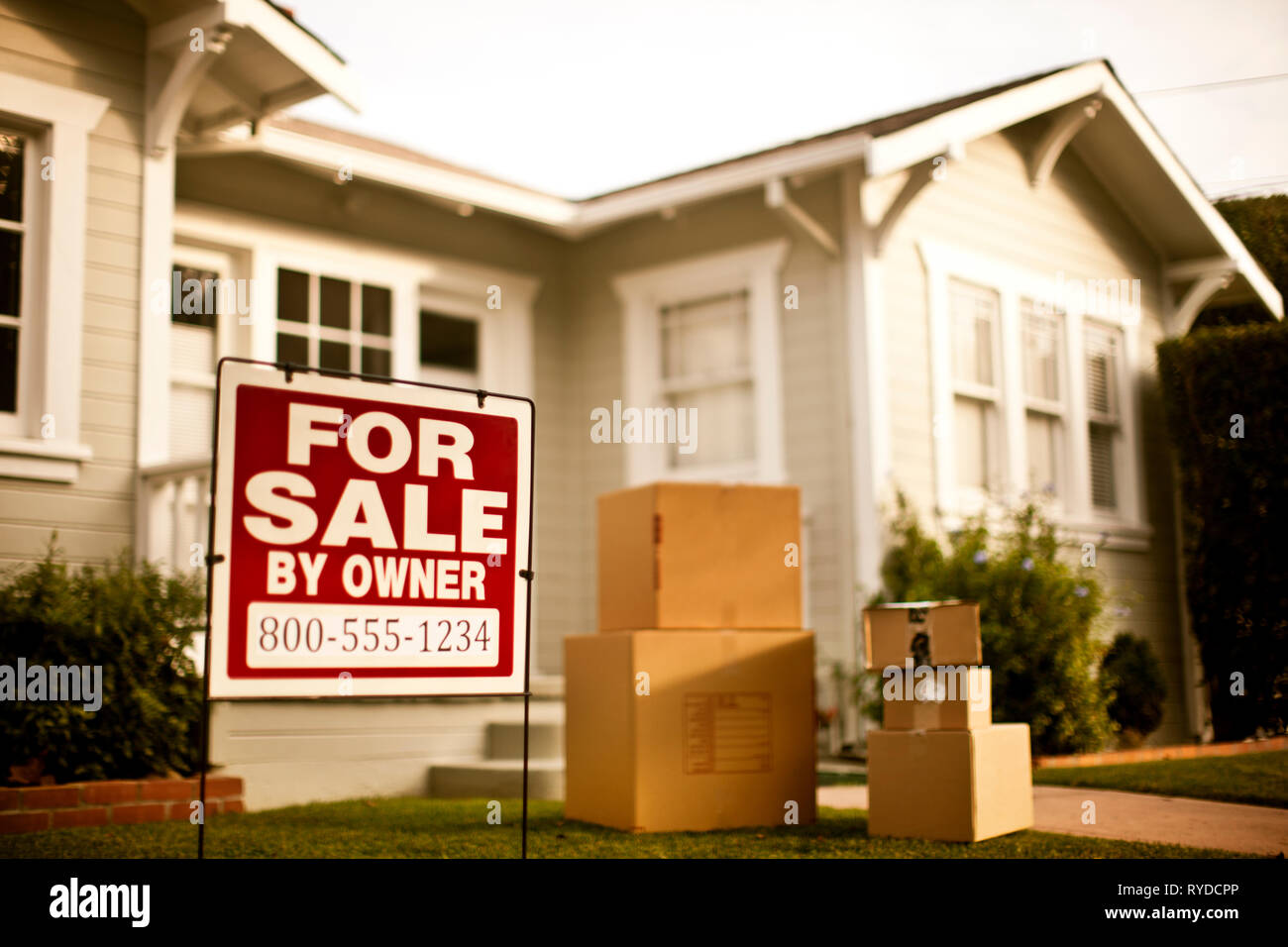 Exterior of house with for sale sign outside. - Stock Image