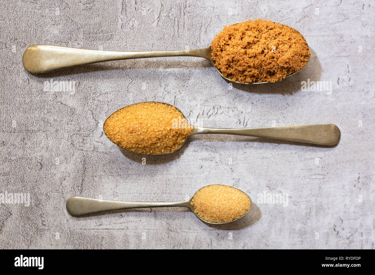 Spoonfuls of demerara, raw and brown sugar. - Stock Image