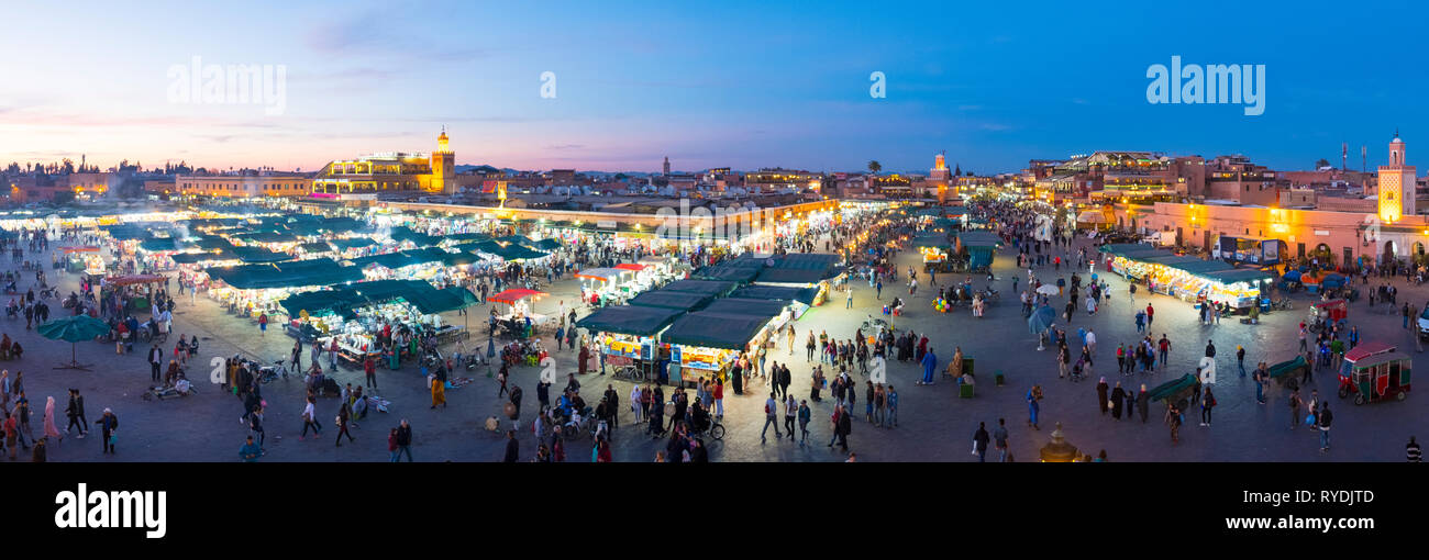 Marrakech, Morocco - March 27, 2018: Panoramic high angle dusk view over Jemaa El-Fna square at evening in historic old town medina Stock Photo