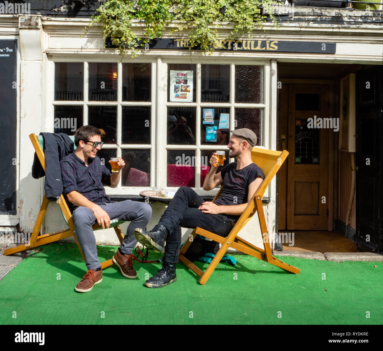 Friends enjoying a beer in the deckchairs outside the Portcullis a local real ale pub in Clifton village Bristol UK - Stock Image