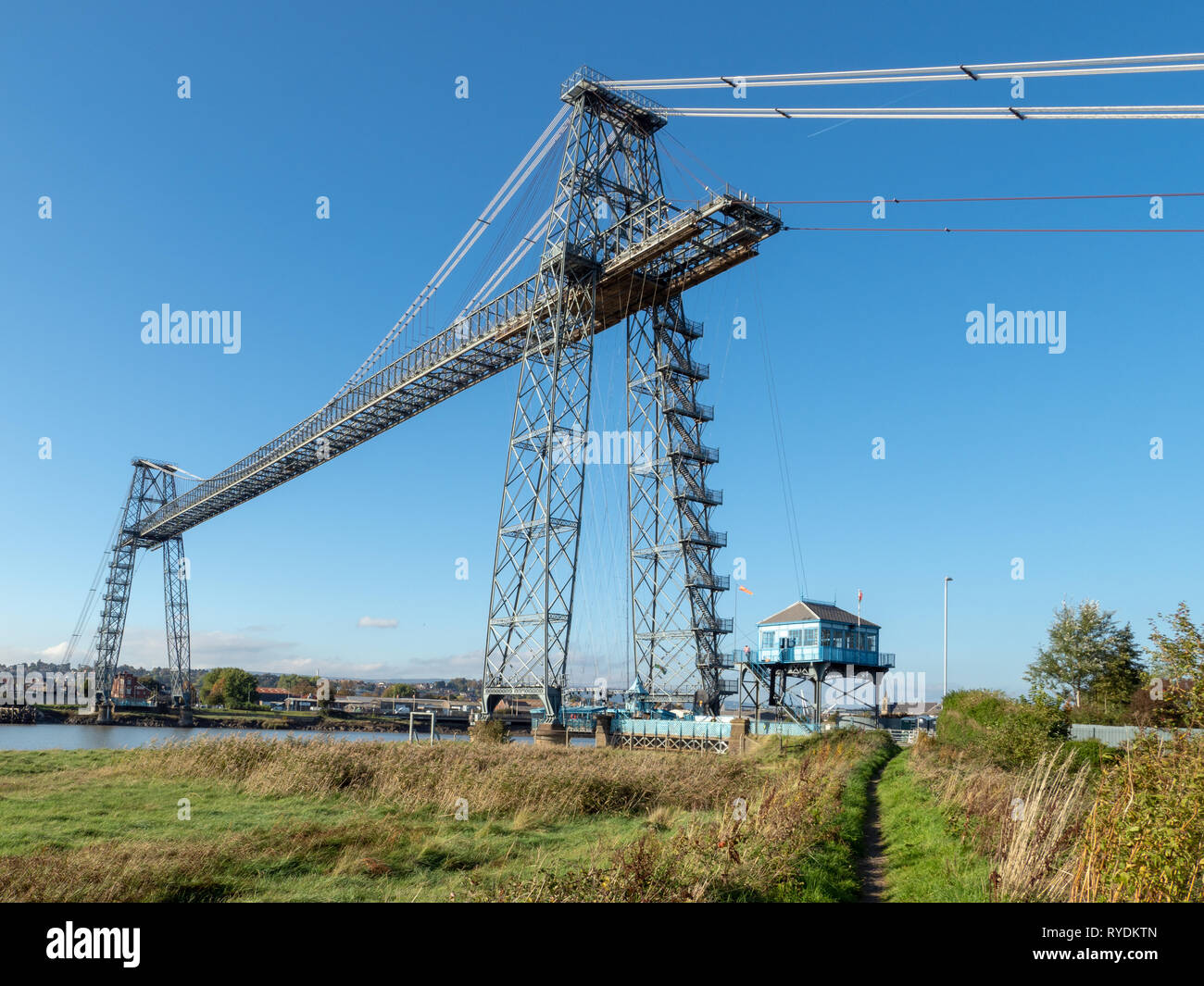 Newport Transporter Bridge spanning the River Usk in South Wales carries vehicles and passengers across the river whilst allowing masted boats beneath - Stock Image