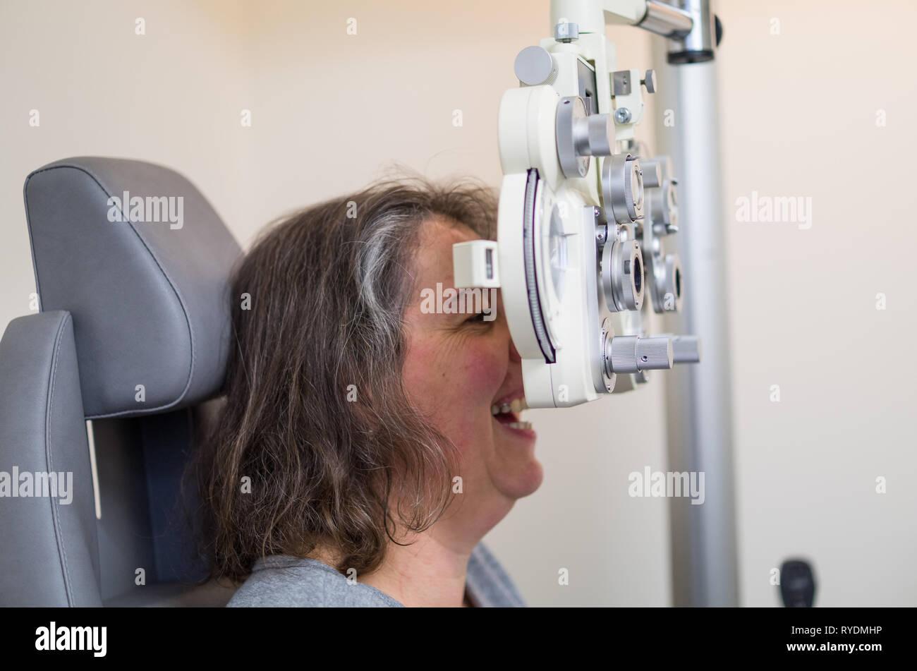 Beim Augenoptiker / Augenarzt / Brille / Augenwerte überprüfen / Frau Sehtest beim Augenoptiker. Stock Photo