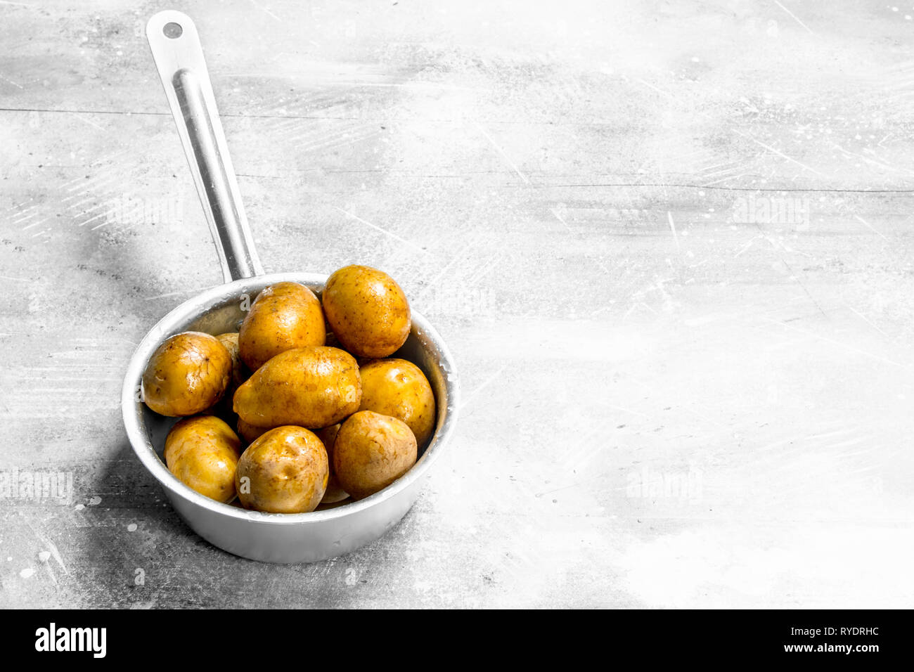 Potatoes in the ladle  On white rustic background Stock
