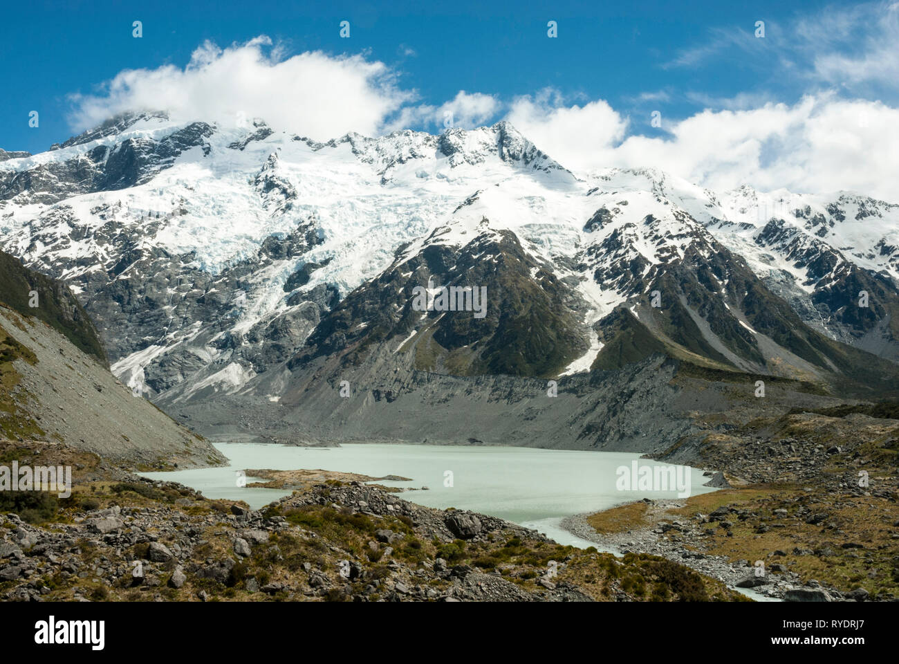 Melt water in Mueller Lake below snow capped Mount Sefton, NZ, in the southern Alps on a sunny day in spring. - Stock Image