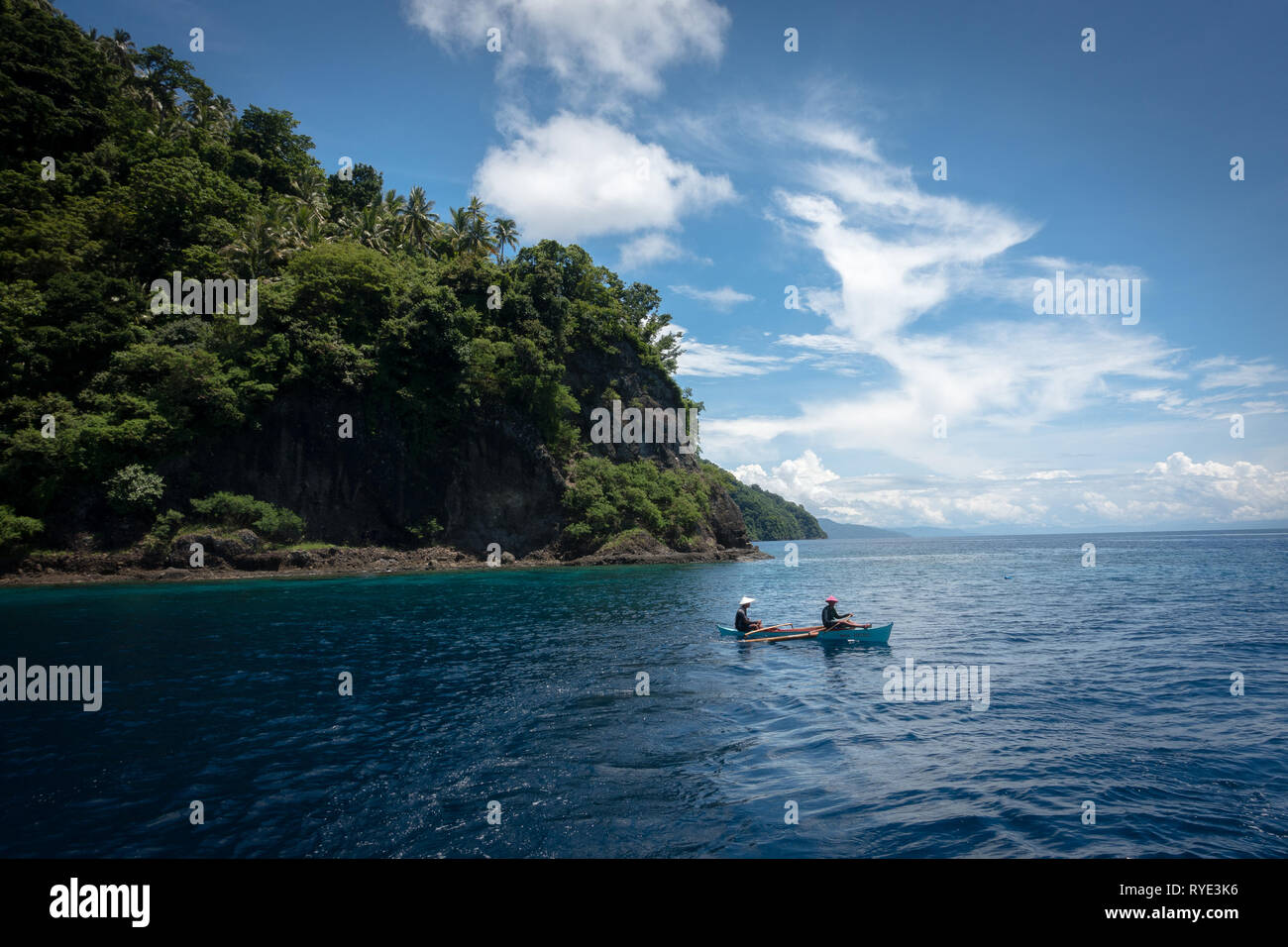 Fishermen with Conical Hat in tiny boat, Padre Burgos Hills - Leyte, Philippines - Stock Image
