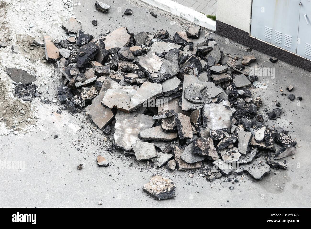 Pile of crushed broken asphalt. City road renewal. Heap of broken road surface - Stock Image