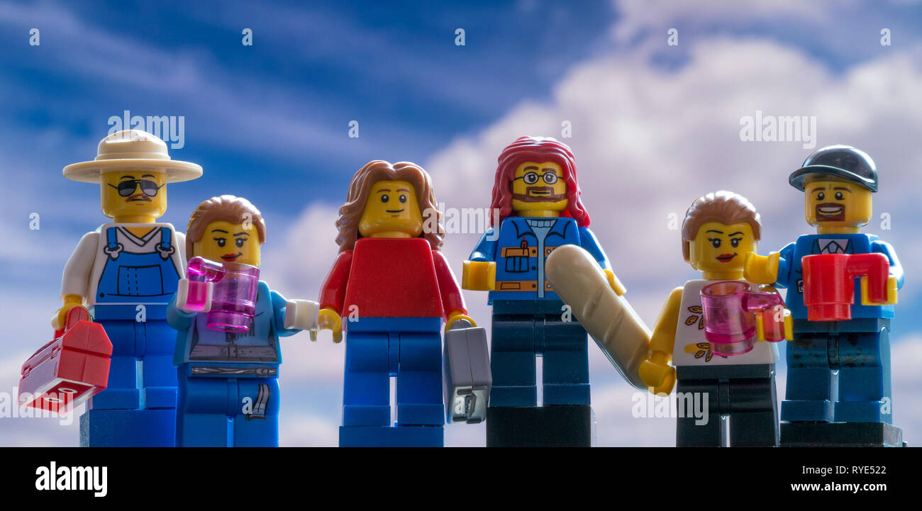 Family of Lego people mini-figures against blue sky background - Stock Image