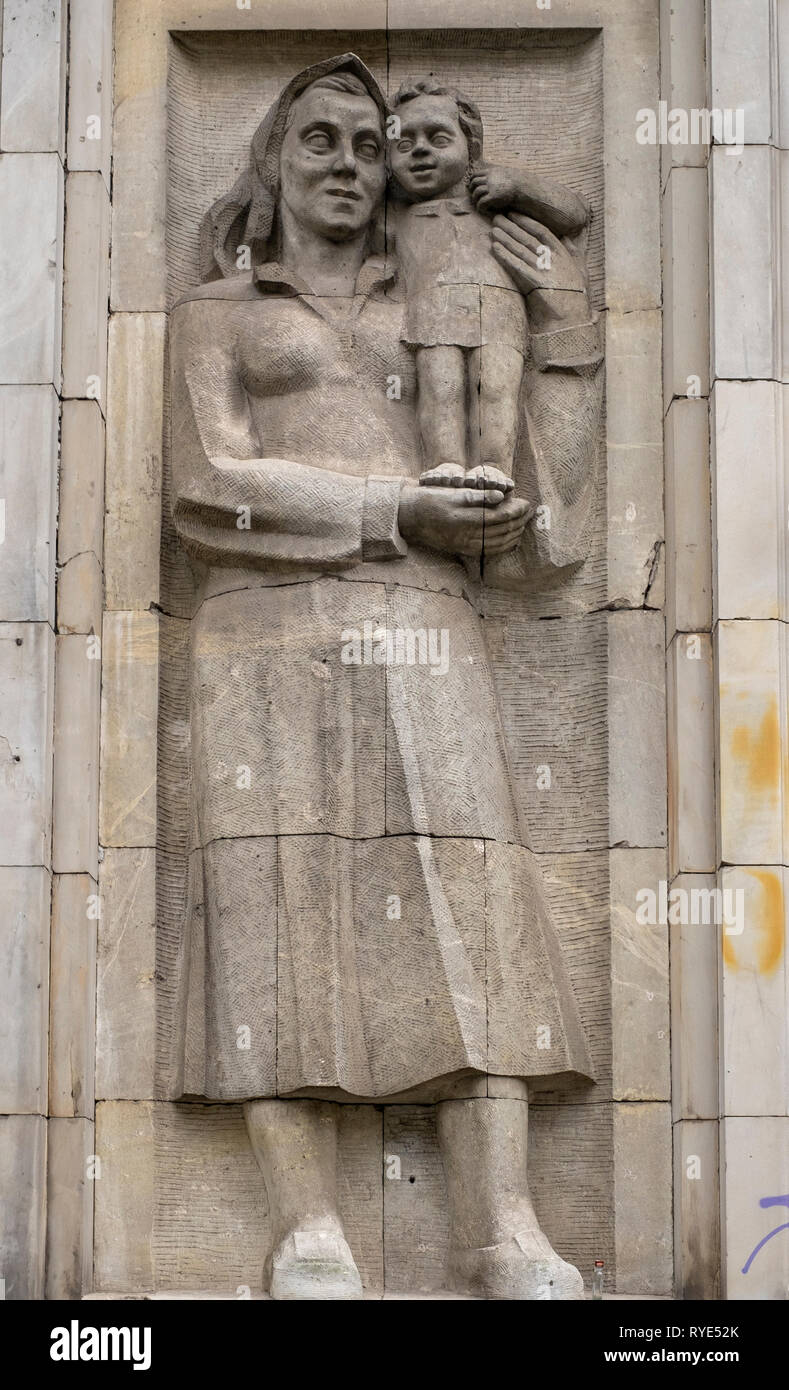 Bas relief of a symbolic depiction of motherhood in the Socialist Realist artistic style near the Constitution Square of Warsaw, Poland. Stock Photo