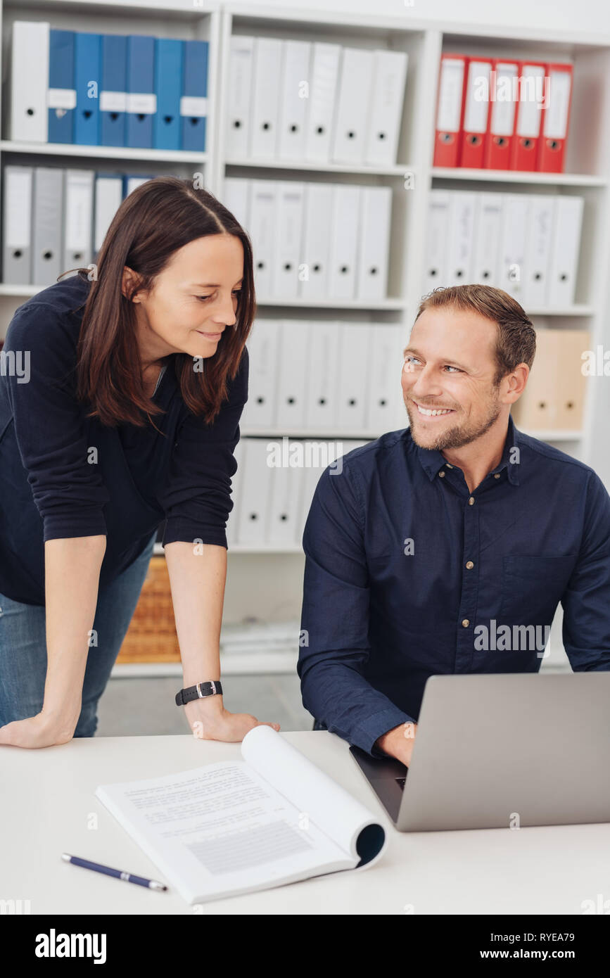Happy businessman smiling at a female colleague as she leans over him as he works at a laptop computer at an office table - Stock Image