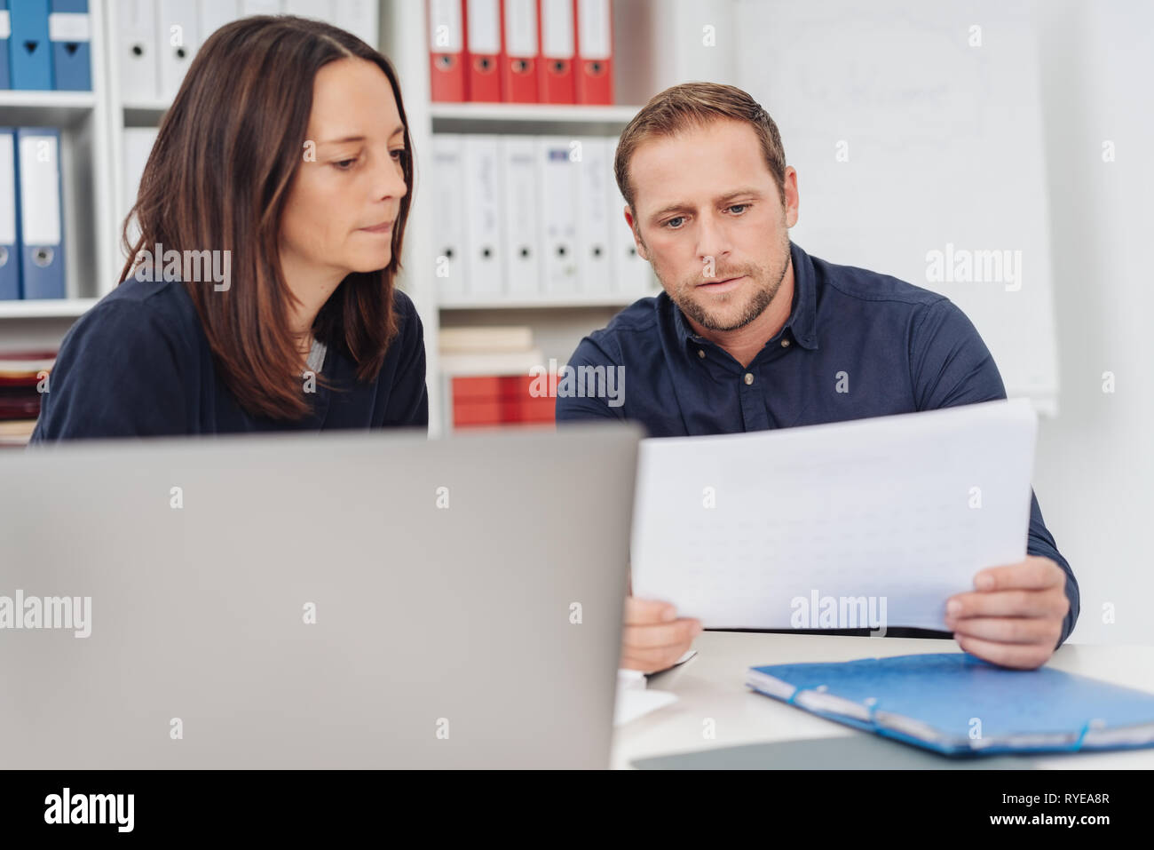 Business partners studying a document together with thoughtful serious expressions as they sit side by side at an office table in a close up view - Stock Image