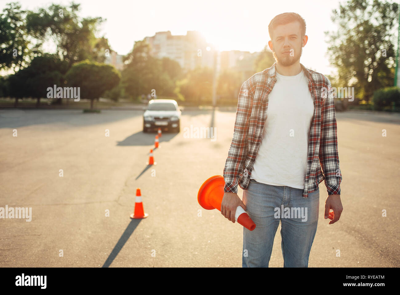 Instructor sets the cone, driving school concept Stock Photo