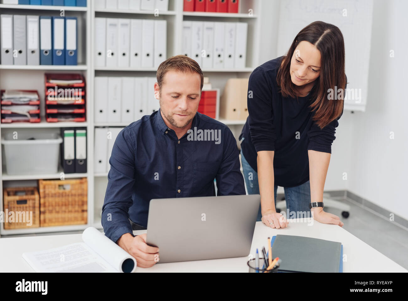 Businessman and woman reading a laptop together in the office with serious expressions as the woman leans over the table alongside her colleague - Stock Image