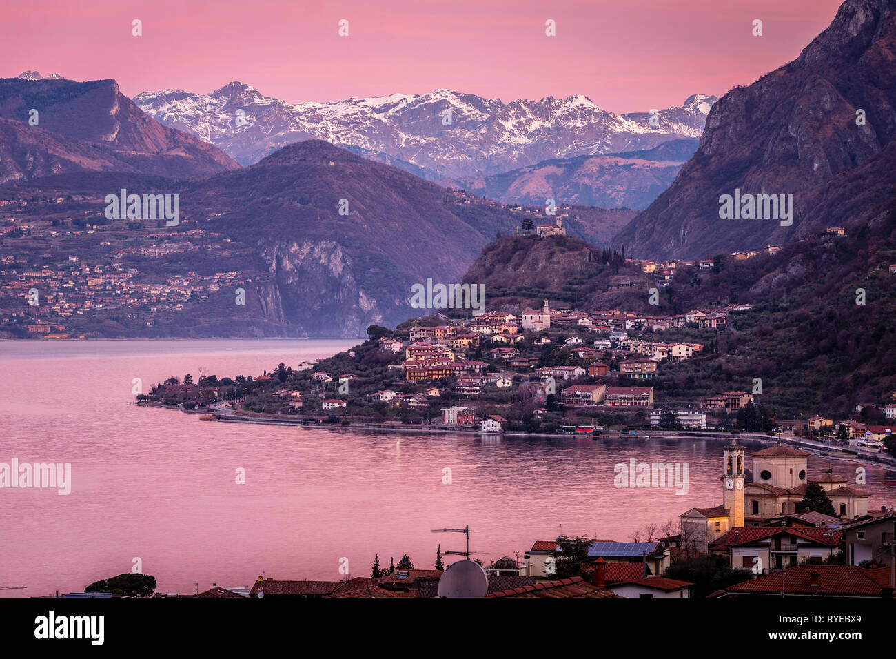 Lake Iseo at dawn, seen from Sale Marasino to the north and the Alps, Lombardy, Italy - Stock Image